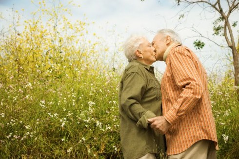 Elderly Couple Kissing in Meadow